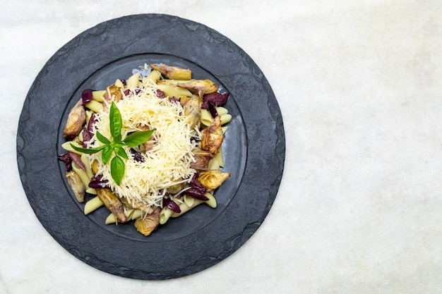 Pasta with black olives parmesan cheese artichoke hearts topped with fresh basil leaves.