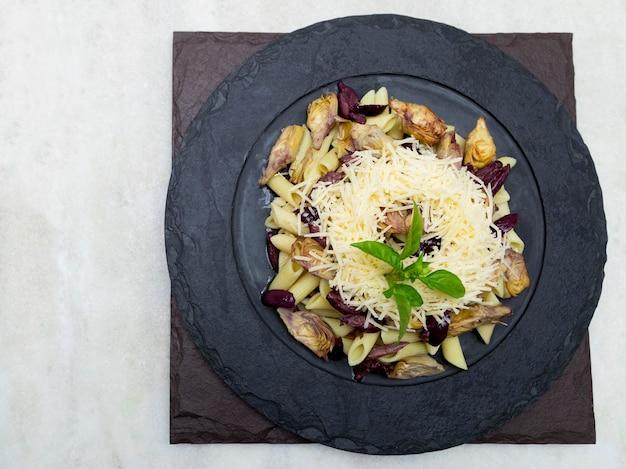ブラックオリーブ、パルメザンチーズ、アーティチョークのハート、新鮮なバジルの葉をトッピングしたパスタ。
