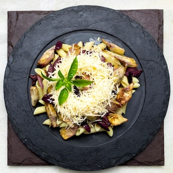 Pasta with black olives, parmesan cheese, artichoke hearts, topped with fresh basil leaves.