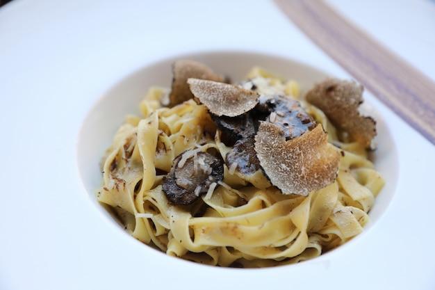 木材の背景、イタリア料理に黒トリュフのパスタ