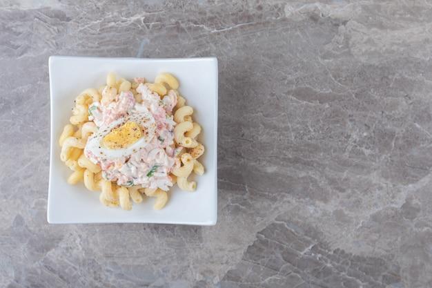 Паста с вареными яйцами в белой миске.