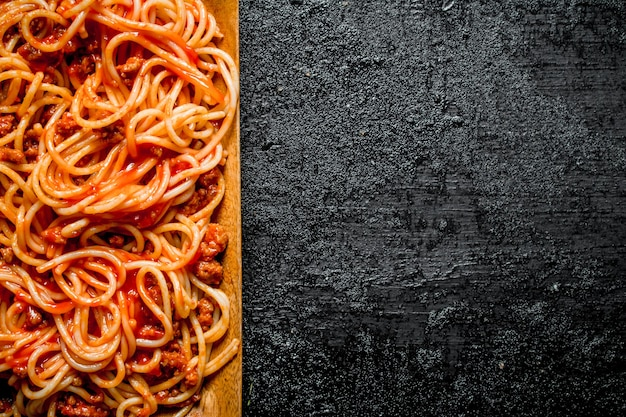 Pasta with bolognese sauce in wooden plate. on black rustic