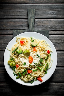 Pasta with brussels sprouts,broccoli and tomatoes. on black wooden background