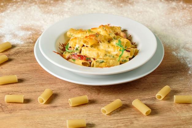 木製のテーブルの上の白いプレートにチーズとトマトソースのパスタ。美しいおいしいレストランの料理。