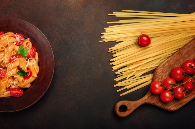 Pasta with cheese and cherry tomato on rusty background.