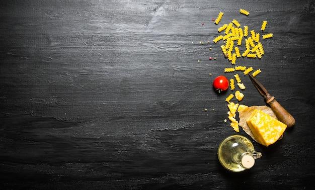 검은 나무 배경에 치즈, 올리브 오일, 토마토와 파스타