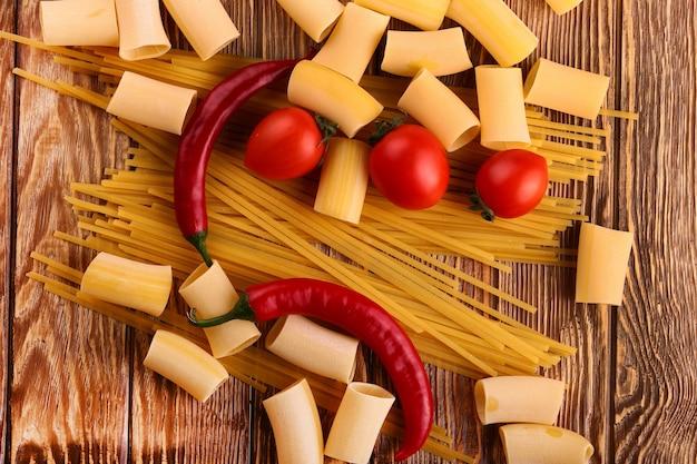 木製のテーブルにミニトマトと他の材料が入ったパスタ(上から見た)
