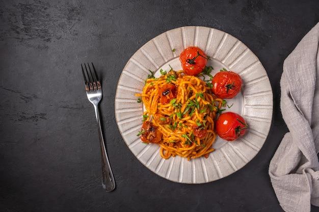 Паста с помидорами черри, сыром и розмарином подается на тарелке с вилкой и салфеткой на темноте