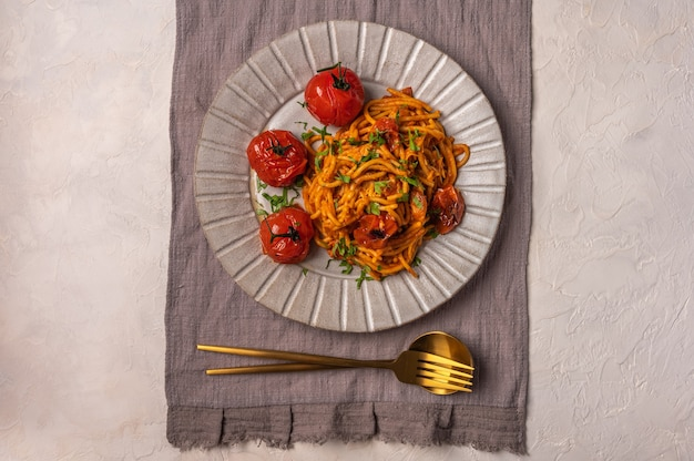 Паста с помидорами черри, сыром и розмарином подается на тарелке ложкой, вилкой и салфеткой.