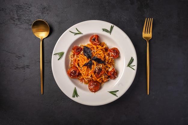 Паста с помидорами черри, сыром и розмарином подается на тарелке ложкой и вилкой на темной текстуре