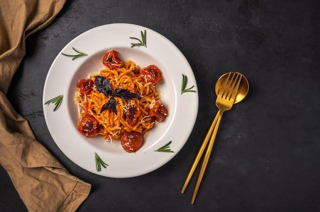 Паста с помидорами черри, сыром и розмарином подается на тарелке с ложкой, вилкой и салфеткой на темноте