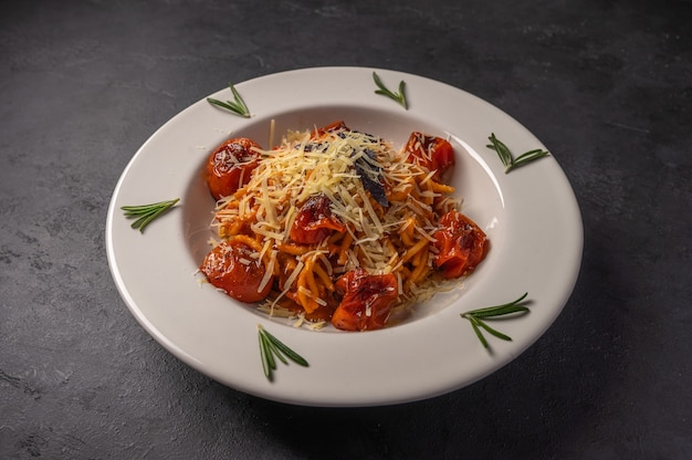 Pasta with cherry tomatoes, cheese and rosemary served on plate on dark textured background, copy