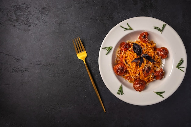 Pasta with cherry tomatoes, cheese and rosemary served on plate with fork on dark textured
