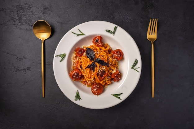 Pasta with cherry tomatoes, cheese and rosemary served on plate with spoon and fork on dark textured