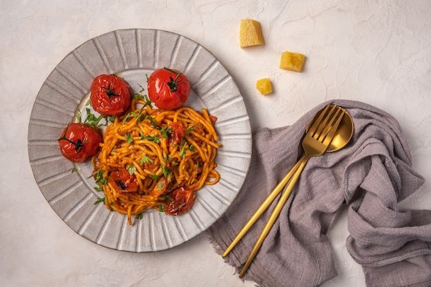 Pasta with cherry tomatoes, cheese and rosemary served on plate with spoon and fork and napkin on