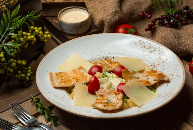 Pasta with chicked grilled slices and tomatoes in white bowl .image