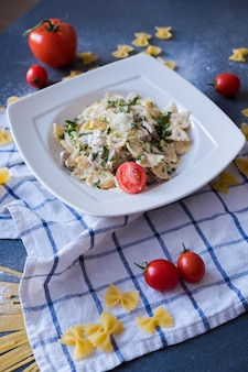 Pasta with chicken, mushrooms, cream, pepper, onion, parsley on white plate