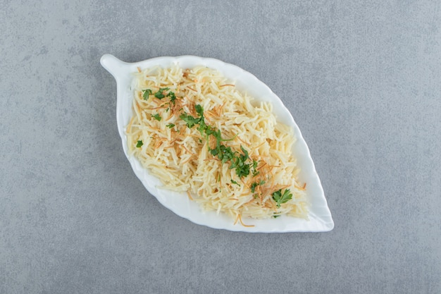 Pasta with chopped parsley on leaf-shaped plate.