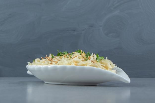 잎 모양의 접시에 다진 파슬리를 곁들인 파스타.