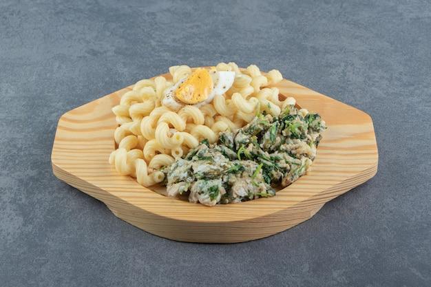 Pasta con deliziose uova sul piatto di legno.