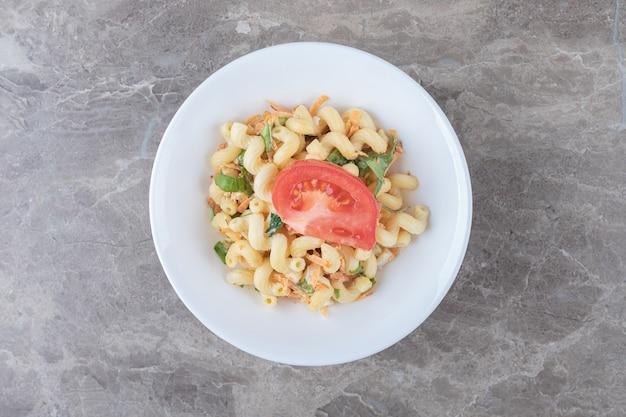 Паста с нарезанными кубиками овощами на белой тарелке.