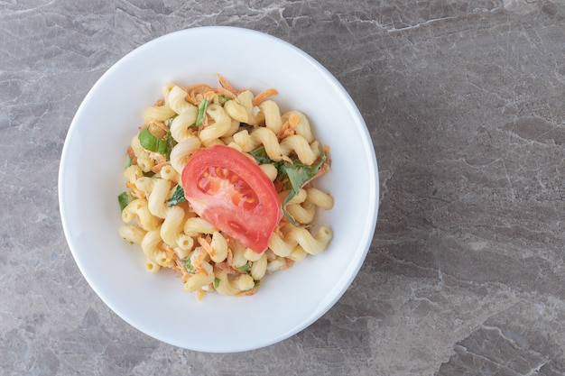 Pasta with diced vegetables on white plate.