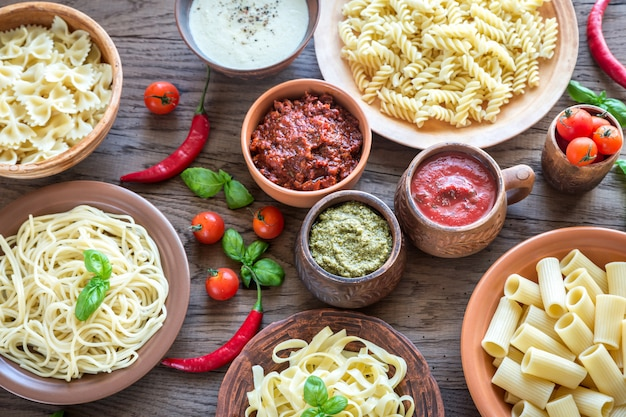 Pasta with different kinds of sauce on the wooden table