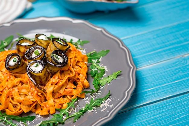 なす、トマト、チーズ、ルッコラのパスタ。シェフによる料理のオリジナルプレゼンテーション。青い木の背景に。