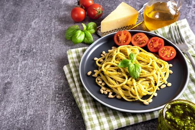 복사 공간이 있는 회색 배경에 신선한 홈메이드 페스토 소스를 곁들인 파스타. 음식 재료 페스토 소스, 토마토, 파마산 치즈, 잣, 신선한 바질 잎을 곁들인 전통 이탈리아 스파게티