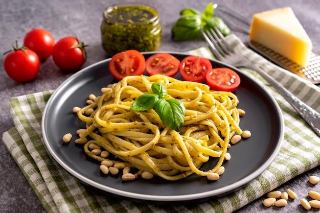 회색 콘크리트 배경에 신선한 홈메이드 페스토 소스를 곁들인 파스타. 음식 재료 페스토 소스, 토마토, 파마산 치즈, 잣, 신선한 바질 잎을 곁들인 전통 이탈리아 스파게티