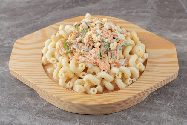 Pasta with fresh salad on wooden plate.