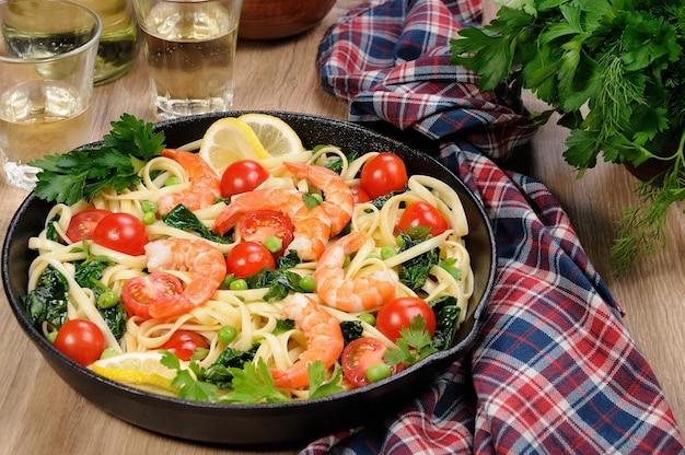 エビフライ、エンドウ豆、トマト、ほうれん草をフライパンに入れ、サイダーグラスのテーブルの上に置いたパスタ。