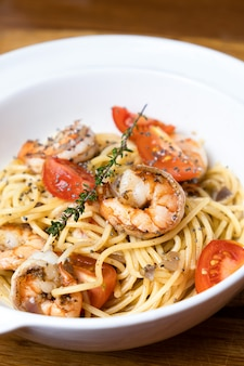 Pasta with fried shrimps and fresh tomatoes.