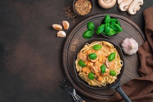 Паста с чесночно-грибным соусом и базиликом на столе из ингредиентов. вид сверху, горизонтальный.