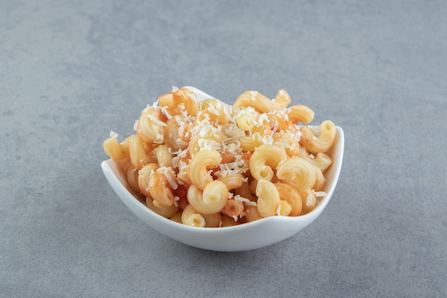 Pasta with grated cheese in white bowl.