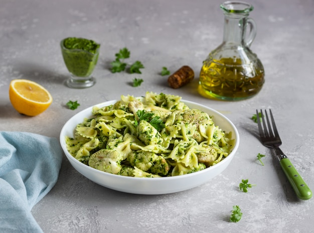 Pasta with green sauce and roaster cauliflower on a white plate. copy space.