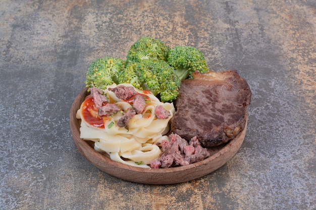 Паста с зеленью и томатной пастой, мясо на белой тарелке