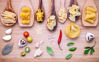 Pasta with ingredients on bamboo cutting board.