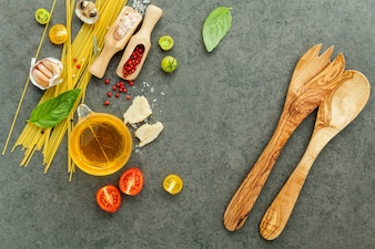 Pasta with ingredients on stone background .