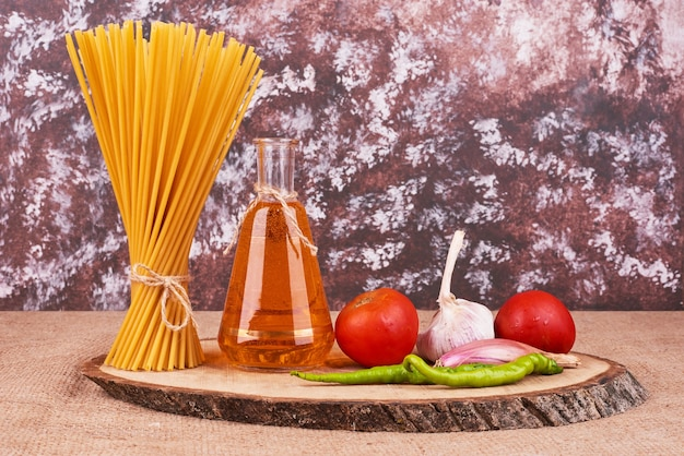 Pasta with ingredients on a wooden board.