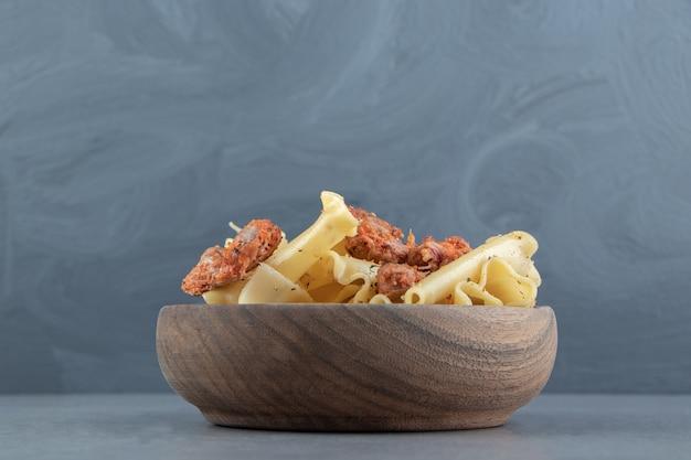 Pasta con parti di pollo marinate in ciotola di legno