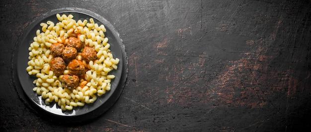 Паста с мясными шариками на тарелке на черном деревенском столе