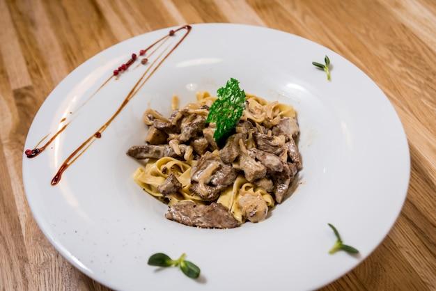 鍋に肉のパスタ。イタリアンスタイルの料理。レストラン。