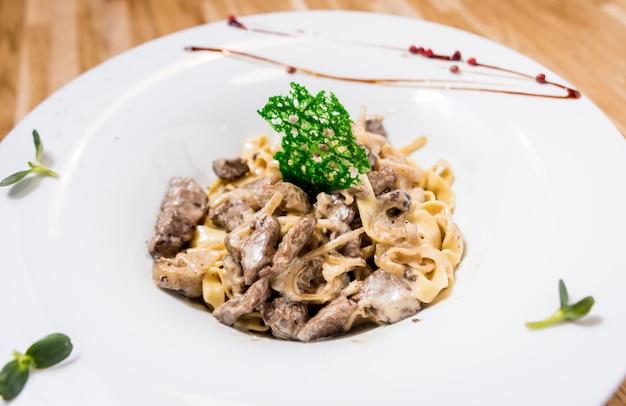 鍋に肉のパスタ。イタリアンスタイルの料理。飲食店。