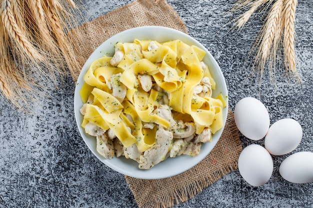 Pasta with meat in a plate with eggs