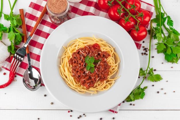 Паста с мясом, томатным соусом и овощами на столе