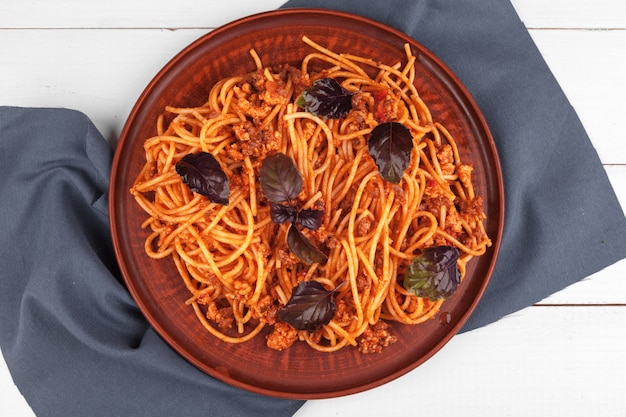 Pasta with meat, tomato sauce and vegetables on the table