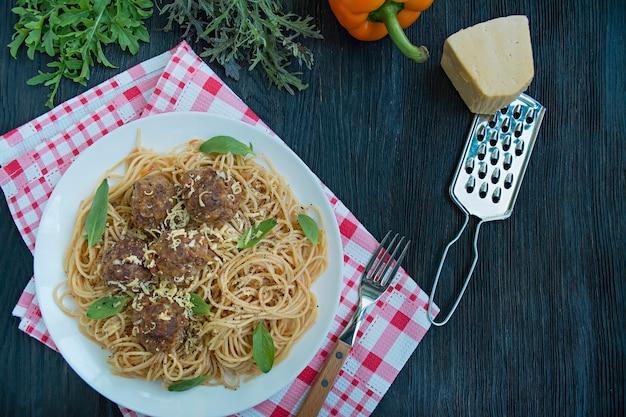 ミートボールとパセリのトマトソースのパスタ。夕食のテーブル。テーブル背景メニュー。暗い背景の木。上面図。テキストのためのスペース。