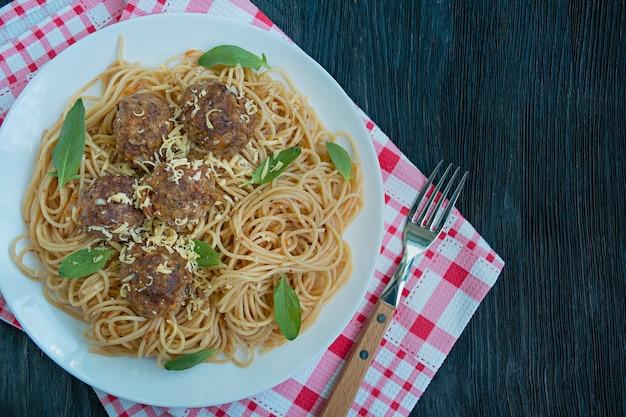 ミートボールとトマトソースのパセリのパスタ。夕食のテーブル。表の背景メニュー。暗い背景の木。上面図。テキスト用のスペース。