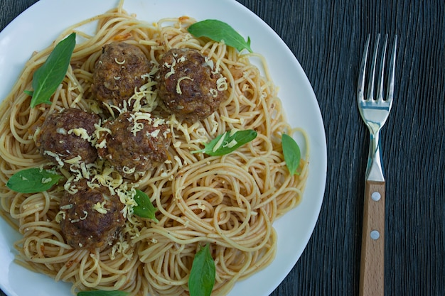 Pasta with meatballs and parsley in tomato sauce.